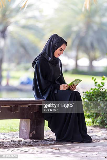 An Arab Woman reading in park, UAE National