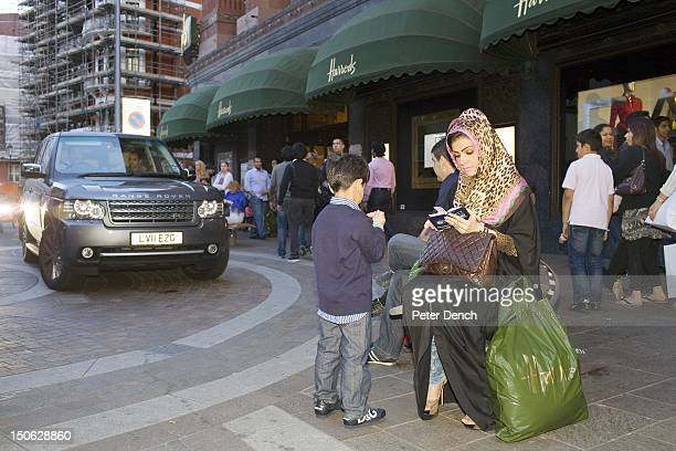 An Arab woman sits on a bench outside Harrod's The Knightsbrdige district store Harrods owned by the Qatar Holding Group is a popular shopping...