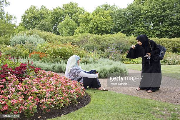 An Arab woman takes photographs in the flower garden at Hyde Park Arabs have been visiting London for centuries and around 300000 Arabs have chosen...