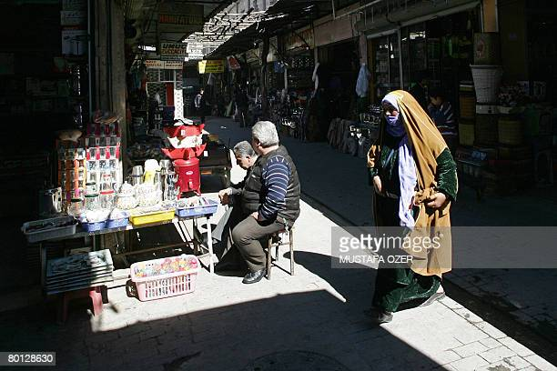 An Arab woman walks in bazaar as shopkeepers chat on March 5 in Turkey's southeastern city of Sanliurfa This Anatolian city has figured in all the...