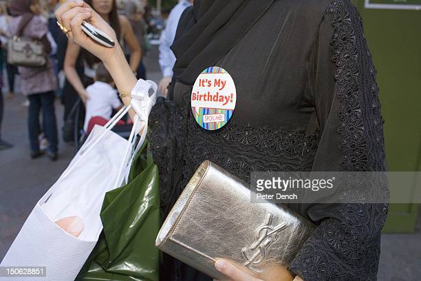 An Arab woman wearing an 'It's Mt Birthday' badge clutching an Yves Saint Lauren bag and a mobile phone outside Harrod's The Knightsbrdige district...