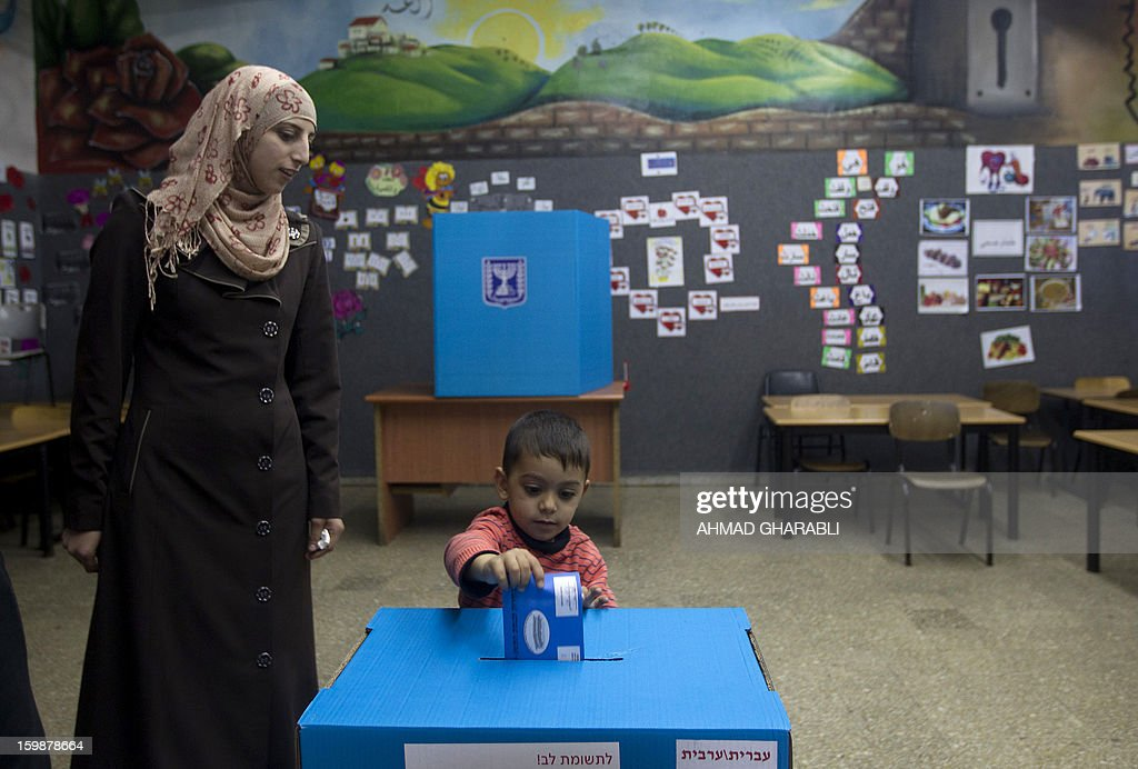 An Arab-Israeli boy casts his mother's ballot at a polling station in the northern Arab-Israeli town of Sakhnin on January 22, 2013. Voters across Israel and in settlements peppering the occupied West Bank cast ballots for the Israeli general election at more than 10,000 polling stations, with turnout standing at 38.3 percent after seven hours of voting. AFP PHOTO/AHMAD GHARABLI