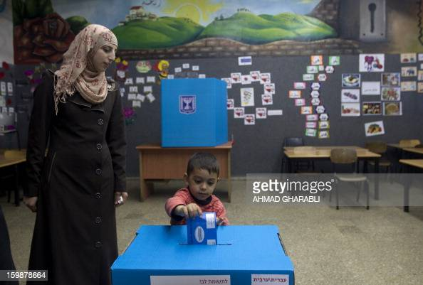 An ArabIsraeli boy casts his mother's ballot at a polling station in the northern ArabIsraeli town of Sakhnin on January 22 2013 Voters across Israel...