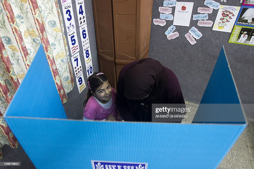 An Arab-Israeli girl stands next to her mother as she marks her ballot at a polling station in the northern Arab-Israeli town of Sakhnin on January 22, 2013. Voters across Israel and in settlements peppering the occupied West Bank cast ballots for the Israeli general election at more than 10,000 polling stations, with turnout standing at 38.3 percent after seven hours of voting.