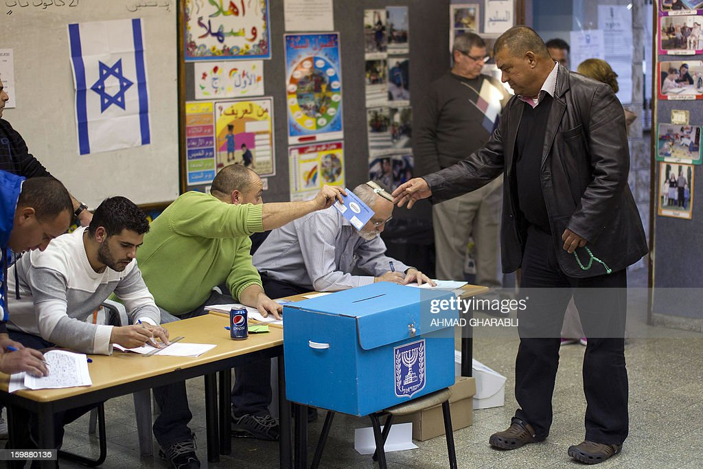 An Arab-Israeli man takes a ballot from a polling station official as he arrives to vote in the northern Arab-Israeli town of Sakhnin on January 22, 2013. Voters across Israel and in settlements peppering the occupied West Bank cast ballots for the Israeli general election at more than 10,000 polling stations, with turnout standing at 38.3 percent after seven hours of voting. AFP PHOTO/AHMAD GHARABLI