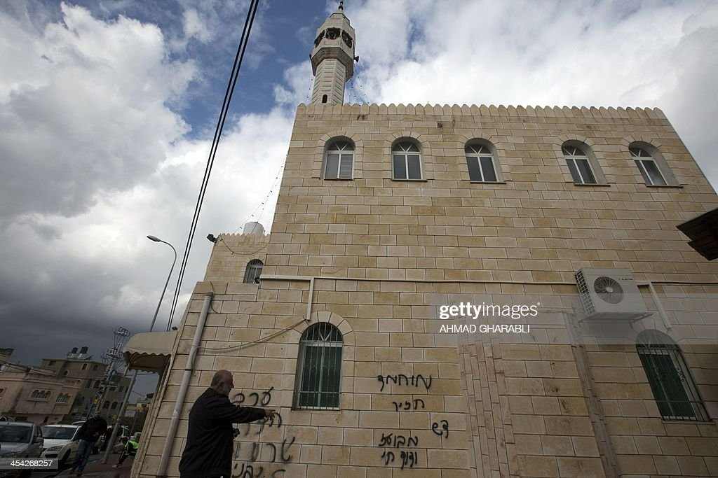 An Arab-Israeli man walks past graffiti sprayed on the walls of a mosque and which reads in Hebrew, 'Mohammed (prophet) is a pig' in the northern Israeli city of Baqa al-Gharbiya on December 8, 2013. Israel and the West Bank have seen a wave of 'price tag' attacks, a euphemism for hate crimes by Jewish extremists which often involve vandalism and in some cases physical injury and which initially targeted Palestinians in retaliation for state moves to dismantle unauthorised settlement outposts in the West Bank, but later became a standard response after any anti-Israeli violence.