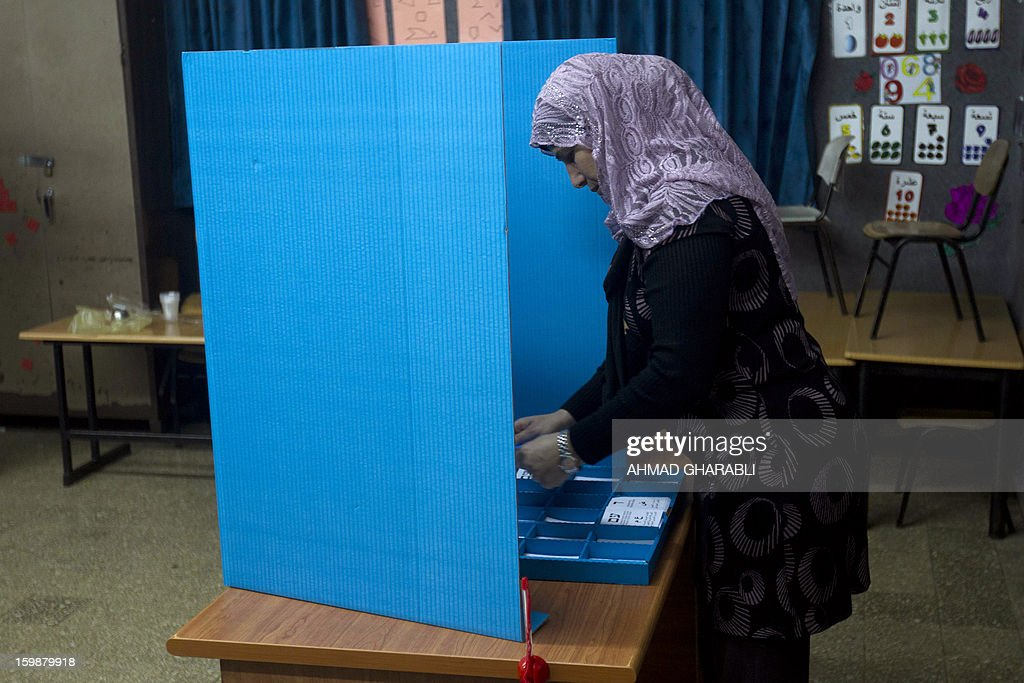An Arab-Israeli woman marks her ballot behind a voting booth at a polling station in the northern Arab-Israeli town of Sakhnin on January 22, 2013. Voters across Israel and in settlements peppering the occupied West Bank cast ballots for the Israeli general election at more than 10,000 polling stations, with turnout standing at 38.3 percent after seven hours of voting. AFP PHOTO/AHMAD GHARABLI
