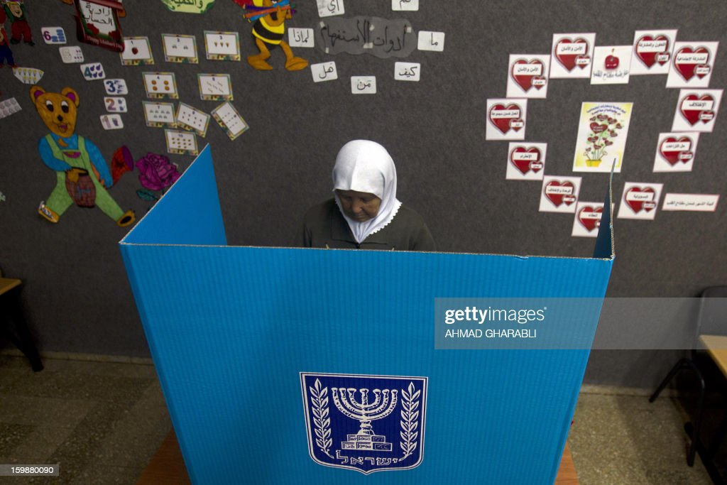 An Arab-Israeli woman marks her ballot behind a voting booth at a polling station in the northern Arab-Israeli town of Sakhnin on January 22, 2013. Voters across Israel and in settlements peppering the occupied West Bank cast ballots for the Israeli general election at more than 10,000 polling stations, with turnout standing at 38.3 percent after seven hours of voting.