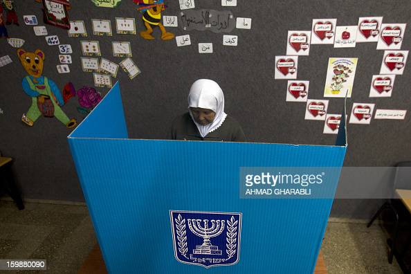 An ArabIsraeli woman marks her ballot behind a voting booth at a polling station in the northern ArabIsraeli town of Sakhnin on January 22 2013...