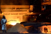 An Arcelor Mittal steelworker takes samples on June 24 2013 during iron casting at one of the two furnaces of the FossurMer plant near the southern...