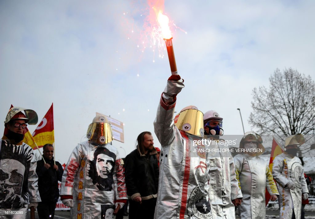 An ArcelorMittal worker (C) holds a flare among other ArcelorMittal workers wearing steelmaker helmets and clothes during a demonstration called by French CGT trade union on February 13, 2013 in Metz, eastern France, to claim for the safeguard of the local industry in the French eastern region of Lorraine.