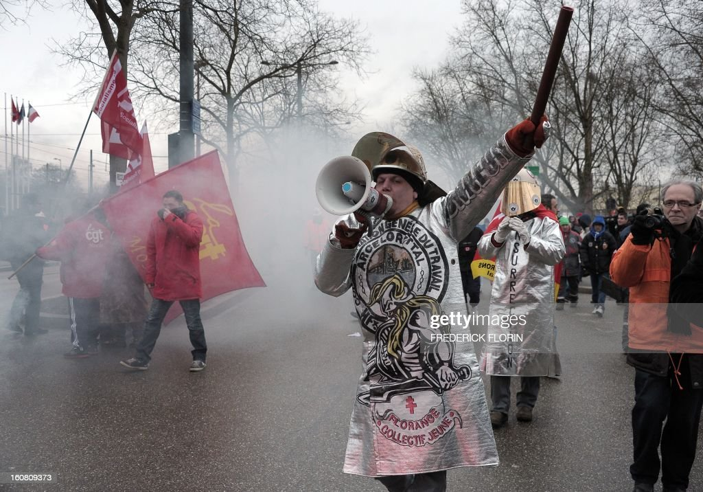 An ArcelorMittal worker speaks in a megaphone on February 6, 2013 during a demonstration of workers from several European steel plants near the European Parliament in Strasbourg, eastern France, cordoned off by anti-riot policemen. The world's top steel producer ArcelorMittal stumbled into the red last year with a net loss of $3.72 billion (2.75 billion euros) largely due to costs related to Europe.