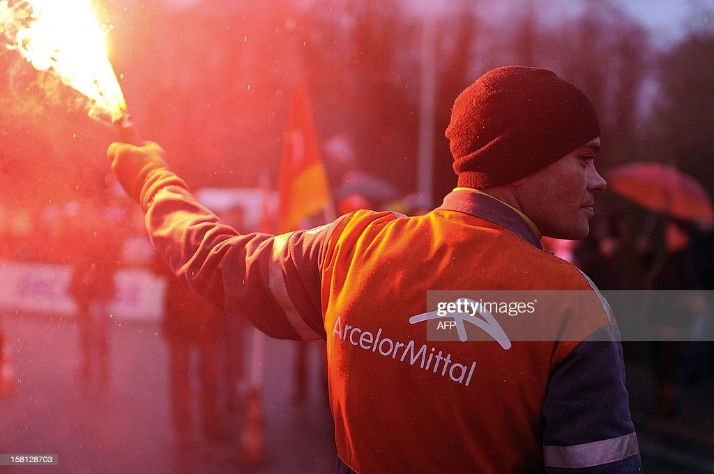An ArcelorMittal's worker holds a flare as workers block the entrance of the Arcelor Mittal Basse-Indre plant on December 10, 2012 in Indre, western France, to protest against the transfer of a part of their activity to the group's plant in Florange.