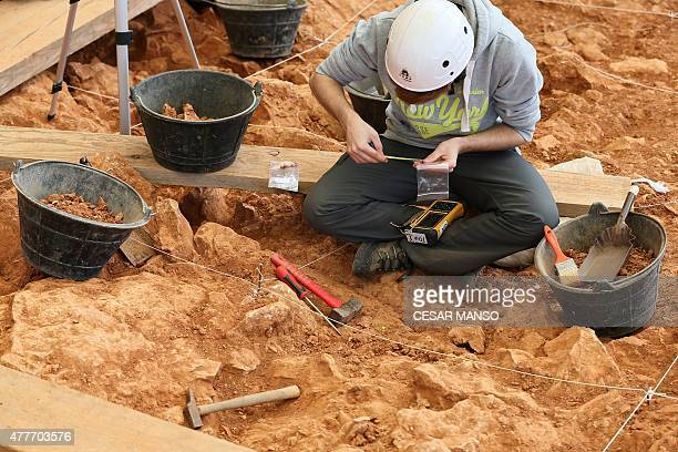 An archaeologist measures an object as he takes part in the beginning of an excavation at the Gran Dolina site part of the archaeological site of...