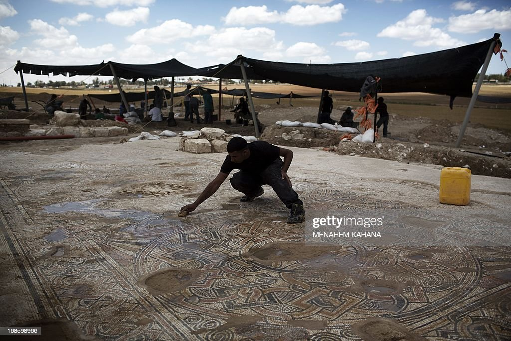An archaeologist of the Israeli Antiquities Authority works on a 1500-year-old Byzantine era mosaic floor near Kibbutz Beit Kama in the Israeli Negev on May 12 2013. The mosaic dating back to the 4th-6th century BC was discovered along with a group of structures under the fields of the Kibbutz Beit before the imminent paving of the southern extension of Highway 6.