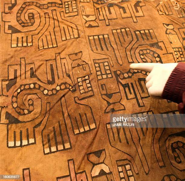 An archaeologist shows the detail of a robe found next to a mummy belonging to the Wari culture at Waca Pucllana in Lima 20 October 2005 The mummy...