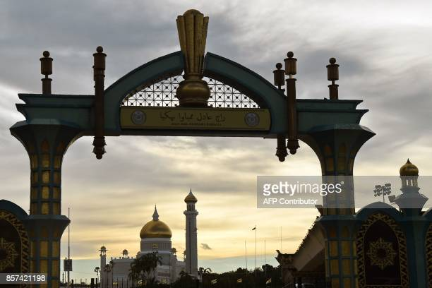 An archway with traditional Jawi and Latin script in Bahasa Melayu reads 'A fair king brings happiness' is seen in front of Brunei's Sultan Omar Ali...