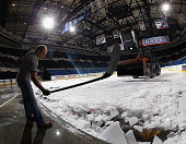 An arena worker uses a hockey stick to help remove ice from the Nassau Coliseum on May 5 2015 in Uniondale New York The New York Islanders have...