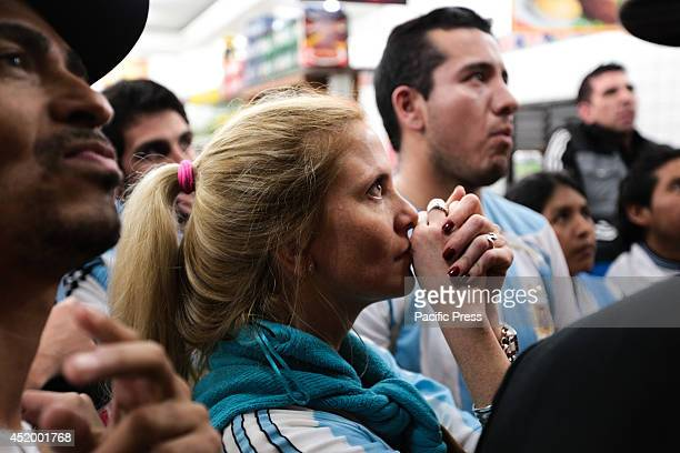 An Argentine fan in the middle of a crowd of fans watch the semifinal World Cup game between Argentina and the Netherlands outside a bar in the...