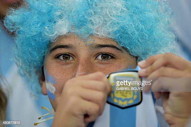 An Argentine fan shows the emblem of the Argentine Football Association as he cheers for his team before the start of a Group F football match...