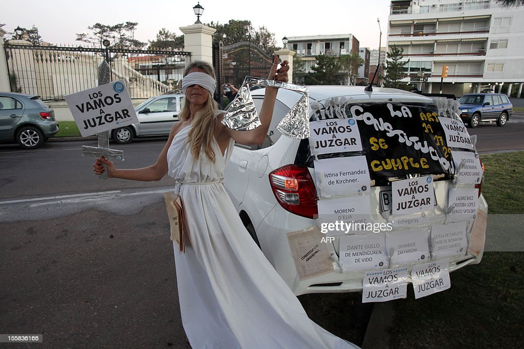 An Argentine takes part in a 'cacerolazo' to protest against the possible reelection of President Cristina Fernandez de Kirchner and the growing insecurity, corruption and restrictions on the purchasing of US dollars, in the Uruguayan seaside resort of Punta del Este, 135 km east of Montevideo, on November 8, 2012. Thousands of opponents of Fernandez de Kirchner gathered in the Argentine capital Buenos Aires and other cities across the world banging their cooking pots in a noisy protest against any possible bid she might run for a third term. 'Say no to reelection,' said the call to protest which was sent across the country via social media websites. Fernandez, 59, is currently barred by the Argentine Constitution from running for a third consecutive term, but her supporters in the Congress have been lobbying for a constitutional amendment.