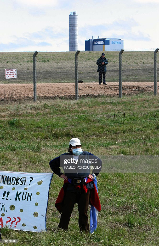 An Argentinian activist wearing a mask demonstrates in front of the Finnish pulp mill (background) site, in the banks of the Uruguay river, near the city of Fray Bentos, 350 km northwest of Montevideo, 02 September, 2007. Argentinian environmentalists crossed the border Sunday to protest against the construction of the pulp mill, as they believe it will pollute the bordering river. AFP PHOTO/Pablo PORCIUNCULA