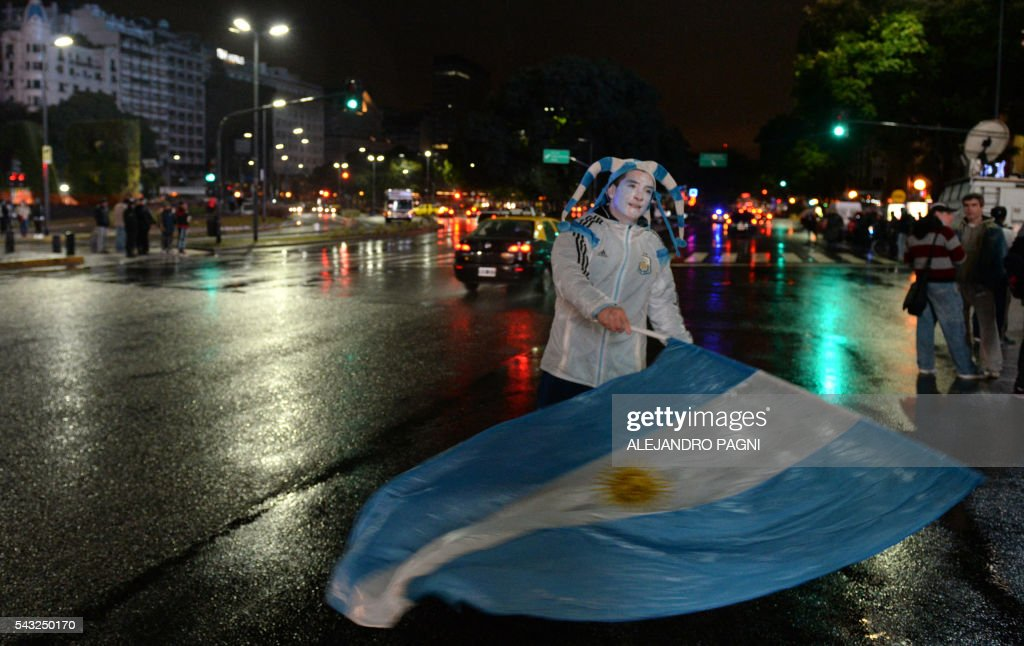 An Argentinian football fans waves the national flag near the Obelisk in downtown Buenos Aires after the Argentina national footbal team was defeated by Chile in penalty kicks in the Copa America Centenario final on June 26, 2016. / AFP / ALEJANDRO
