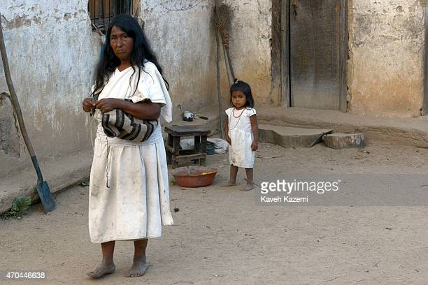 An Arhuaco woman dressed in white weaves a mochila handbag while walking in the courtyard outside her house followed by her grandchild on January 24...