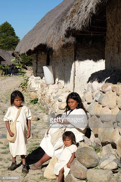An Arhuaco woman with her children all dressed in white sits outside a hut in the walled village on January 24 2015 in Nabusimake Colombia Nabusimake...