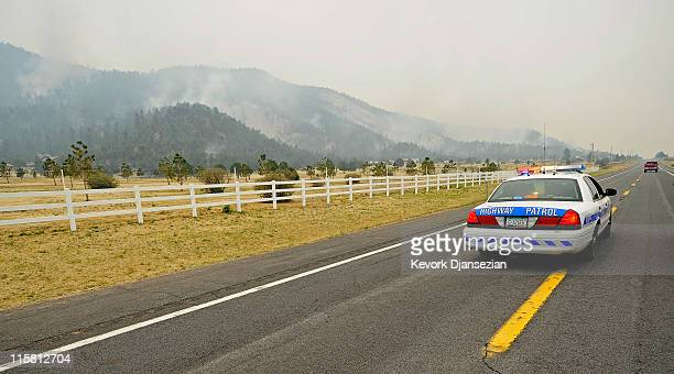 An Arizona Highway Patrol car travels along US Highway 191 as the Wallow Fire burns in the hillsides on June 10 in Nutrioso Arizona The fire which is...
