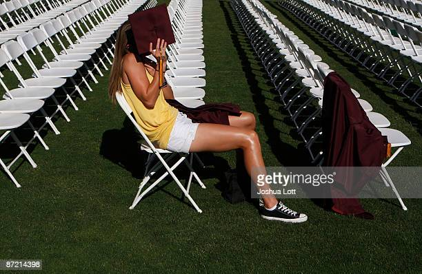PHOENIX AZ MAY 13 An Arizona State University graduate student uses her cap to block the sun during her graduation at Sun Devil Stadium May 13 in...