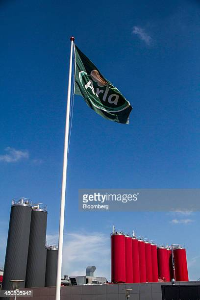 An Arla branded flag flies near storage silos at the Arla Foods amba butter factory in Holstebro Denmark on Tuesday June 17 2014 Arla Foods the...