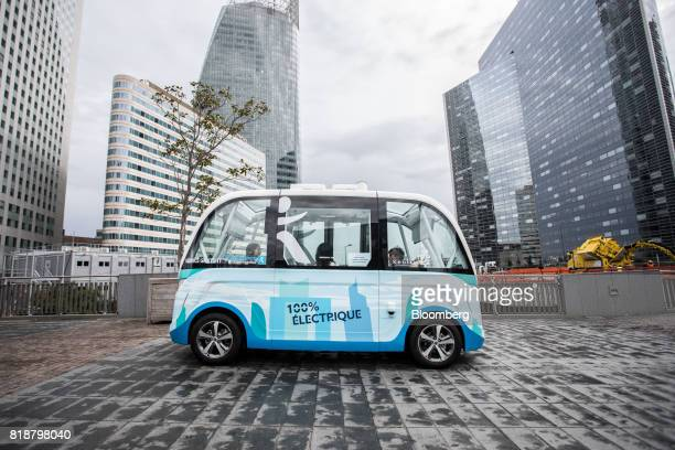 An Arma autonomous shuttle bus manufactured by Navya Technologies SAS passes skyscrapers as it travels in La Defense business district of Paris...
