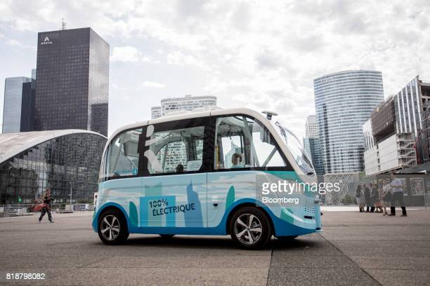 An Arma autonomous shuttle bus manufactured by Navya Technologies SAS travels as skyscrapers stand in La Defense business district of Paris France on...