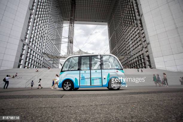 An Arma autonomous shuttle bus manufactured by Navya Technologies SAS passes the Grande Arche monument as it travels in La Defense business district...