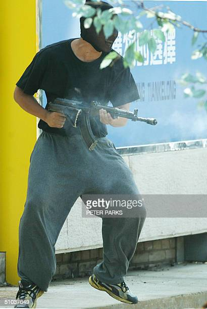 An 'armed bank robber' 'fires' an AK47 at police in an exercise in a police training school on the outskirts of Beijing 09 July 2004 The exercise was...