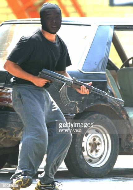 An 'armed bank robber' with an AK47 runs from police in an exercise in a police training school on the outskirts of Beijing 09 July 2004 The exercise...