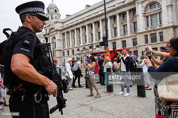 An armed British police officer on security patrol among tourists at Horse Guards Parade in London UK on Friday July 15 2016 Eight months after a...