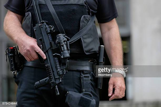 An armed British police officer on security patrol outside the Ministry of Defence in London UK on Friday July 15 2016 Eight months after a murderous...