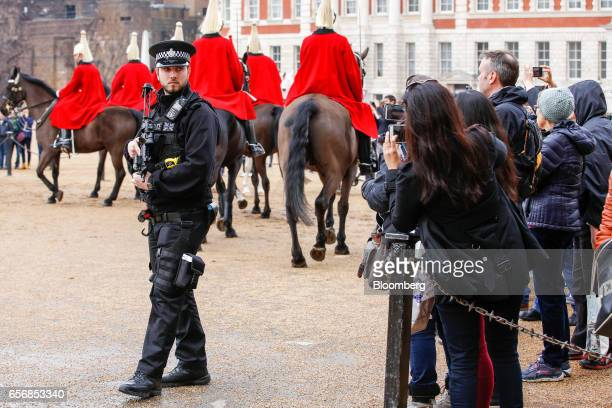 An armed British police officer patrols in Horse Guards Parade as tourists watch guards passing by on horseback after the terror attack at...