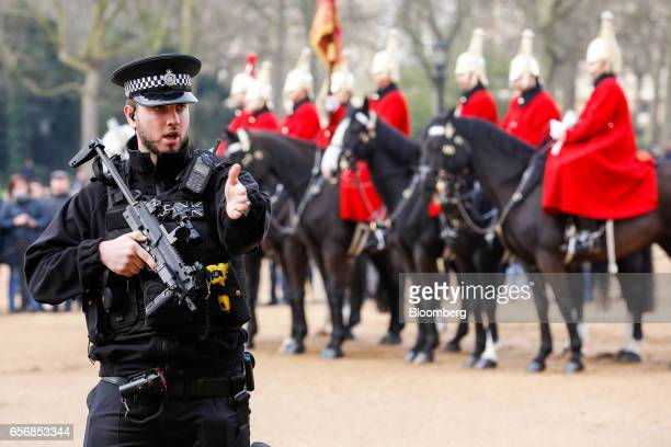 An armed British police officer patrols in Horse Guards Parade as tourists watch after the terror attack at Westminster in central London UK on...
