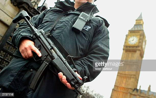 An armed British police officer stands gaurd outside the Houses of Parliament on November 17 2003 in London The unprecedented policing operation that...