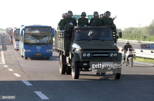 An armed escort leads a convoy of buses transporting a group of Chinese prisoners to a newly constructed prison in Shenyang in northeastern China's...