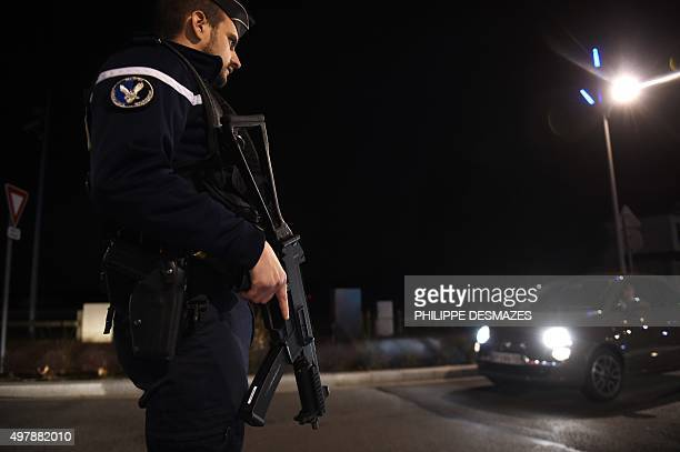 An armed French gendarme stands guard during the control of vehicles at the FrenchSwiss border in DivonnelesBains near Geneva on November 19 2015...