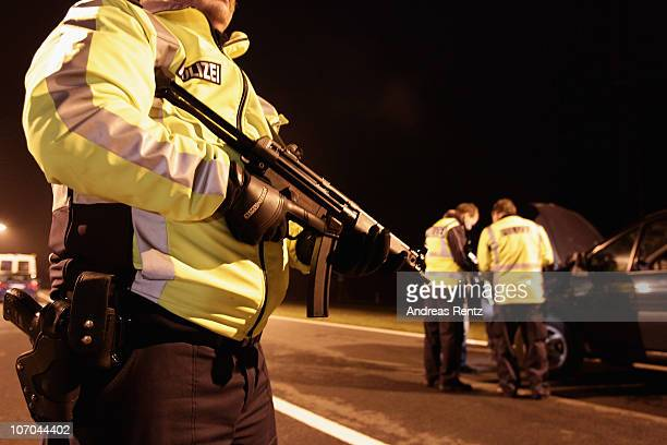 An armed german policeman secures as police officers control a car driver during a traffic control on November 21 2010 in Walsleben near Berlin...