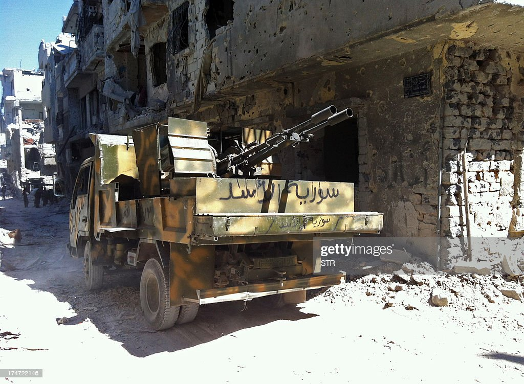 An armed government forces vehicle with text on it reading in Arabic: 'Assad's Syria', which refers to Syria's President Bashar al-Assad, is seen in the Khalidiyah neighbourhood of Syria's central city of Homs on July 28, 2013. Government forces bolstered by Lebanese Shiite militiamen were poised to retake the largest rebel-held district of Syria's third city Homs, a watchdog and state media said. AFP PHOTO/STR
