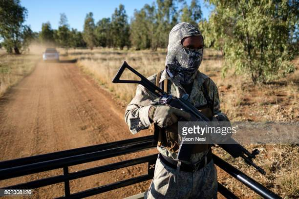 An armed guard rides in the back of a truck at the ranch of rhino breeder John Hume on October 16 2017 in the North West Province of South Africa...