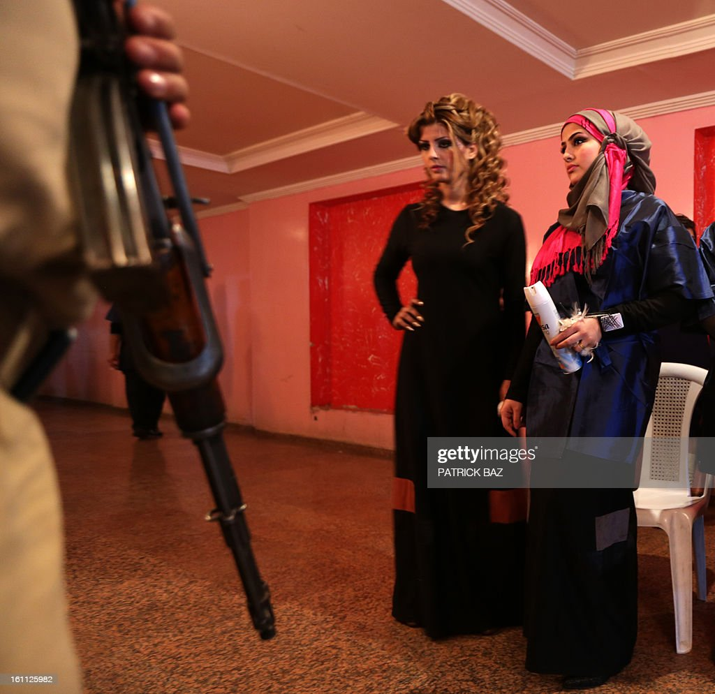 An armed guard stands at the door in front of Iraqi model during a hairdressers and make up artists festival on February 9, 2013 in Baghdad. It is the first time that this kind of festival takes place in the Iraqi capital since 1999.