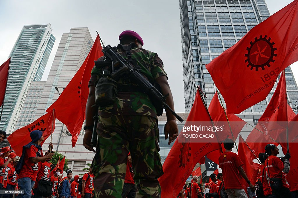 An armed Indonesian soldier stands along the roadside while thousands of workers (background) march to the presidential palace in Jakarta on May 1, 2013 to mark Labour Day in protest against outsourcing policy and low wages. According to the police about 55,000 workers participated in the Labour Day rally while thousands of police and troops were mobilized for security.