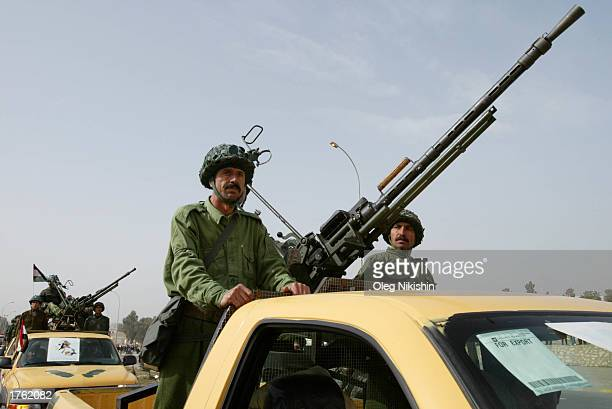 An armed Iraqi man rides in a car during a parade in Mosul north of Baghdad February 4 2003 Thousands of armed volunteers paraded in northern Iraq in...